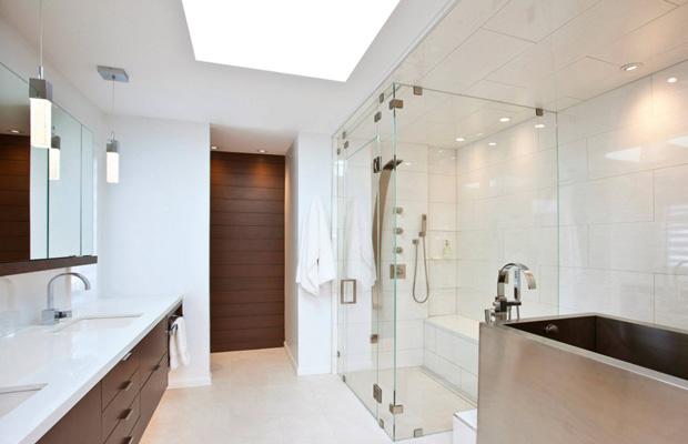 Стильная ванная комната в многоквартирном доме со стеклянной душевой
