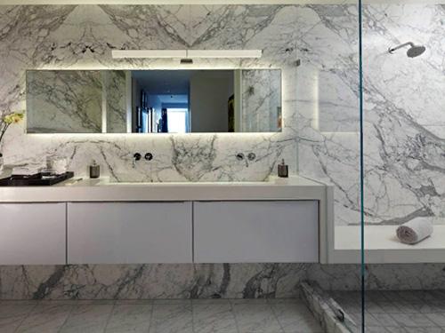 Интерьер ванной комнаты с перегородкой из стекла и подвесного шкафа