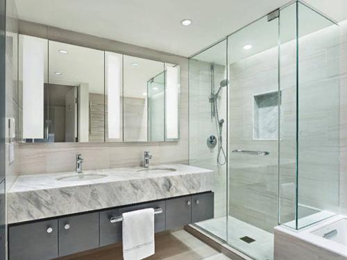 Интерьер ванной комнаты где установлена перегородка из стекла с душем
