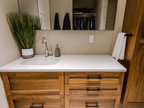 Дизайн ванной комнаты с мебелью из дерева и стеклянной душевой